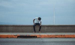 一個人低頭的坐在馬路旁