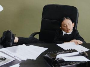 小女孩躺在辦公椅上 桌上有許多文件