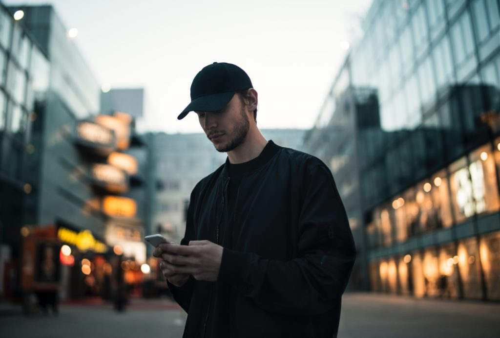 一個穿黑衣的男人在城市中滑手機